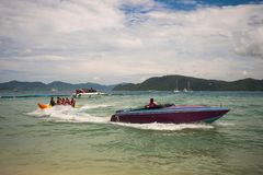 Coral Island Koh He A high-speed motor boat rides tourists on a banana. A high-speed motor boat rides tourists on a banana Stock Photos
