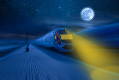 High Speed Night Train. High-speed train passing station with motion blur, moon and stars in night sky Stock Photo