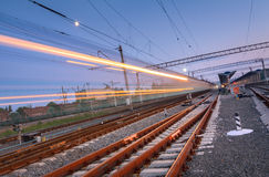 High speed passenger train on railroad track in motion. At night. Blurred commuter train in railway platform. Railway station with blue sky. Railroad travel Royalty Free Stock Photos