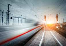 High speed passenger train on railroad track in motion. At sunset. Blurred commuter train. Railway platform in the city. Railway station in Europe. Railroad Stock Photos