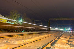 High speed passenger train on railroad tracks with motion blur effect near the railway station Stock Photo