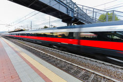High speed passenger trains on railroad platform in motion. Blur effect of commuter train. Railway station in Florence, Italy. Stock Images