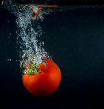 High speed photography tomato splash in water over black Stock Photos