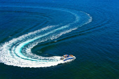 High-speed pleasure boat. In dark blue sea with trail Royalty Free Stock Photo