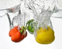 High-speed raw food. Deliciousness and energy of raw food rich in biophotons. Green, yellow and red peppers splash in the water royalty free stock images