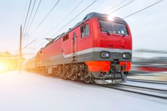 High-speed red locomotive passenger train rides at high speed in winter around the snowy landscape. royalty free stock image