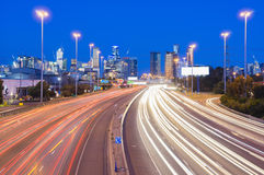 High speed traffic and light trails in highway at twilight Stock Photo