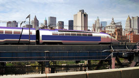 High speed train. A high-speed modern train arriving to the city, while it finishes to cross a bridge stock image