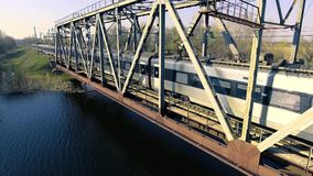 A high-speed train drives a bridge across the river stock footage