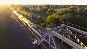 A high-speed train drives a bridge across the river at sunset stock footage