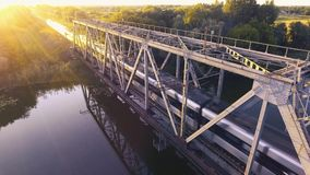 A high-speed train drives a bridge across the river at sunset. Aerial view 4K stock footage