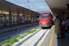 The high-speed train Frecciarossa ETR.1000 of the Trenitaliya company arrives to the platform of the central railway sta, Florence. FLORENCE, ITALY - SEPTEMBER Stock Image