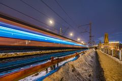 High-speed train with motion blur on the background of the railway bridge in the dark stock photography