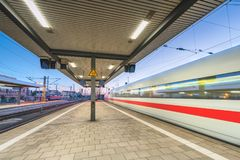 High speed train in motion on the railway station at night Stock Image