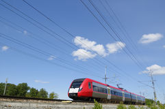 High-speed train on the move. High-speed bullet-train on the move, surrounded by countryside and blue-sky Royalty Free Stock Images
