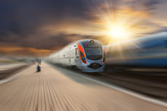 High-speed train passing station. With motion blur, majestic clouds and sun on background Stock Images