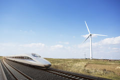 High speed train passing Wind mill land Royalty Free Stock Photography