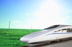 High speed train passing windmill Stock Photography