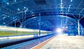 The high speed train raced past the station. At night, the high-speed train passing station Stock Photos
