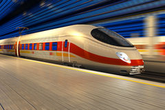 High speed train at the railway station. Modern high speed train departs from railway station at night with motion blur effect Stock Images