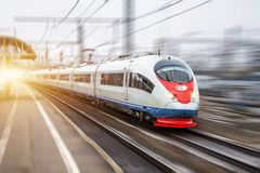 High speed train rides at high speed at the railway station in the city. stock image