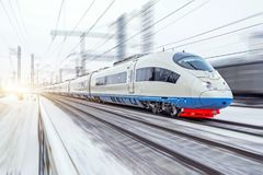 High-speed train rides at high speed in winter around the snowy landscape. stock photos
