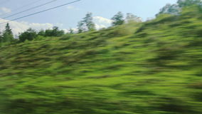 High-speed trains on the hillside and trees (POV) Stock Photo