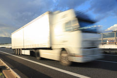High speed truck transportation concept. Motion blurred white truck on highway Royalty Free Stock Image