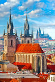 High spires towers of Tyn church in Prague city. Church of Our Lady before Tyn cathedral urban landscape panorama with red roofs of houses in old town and blue Royalty Free Stock Photography