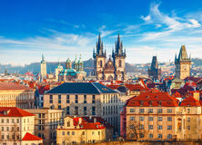 High spires towers of Tyn church in Prague city. Church of Our Lady before tyn cathedral urban landscape panorama with red roofs of houses in old town and blue stock photography