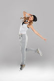 High-spirirted young woman dancing. High-spirited beautiful young woman in casual clothes and trainers dancing and leaping in the air with a pair of music Stock Photography