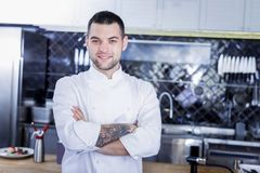 High-spirited handsome cook standing in the kitchen royalty free stock images