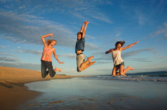 High spirited teens jumping. Teenagers leap high into the air at an unspoiled beach in South Africa Royalty Free Stock Images