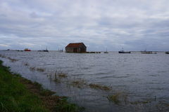 Tidal Surge at Thornham. Flood tide on the Norfolk coast at Thornham engulfing the harbour and barn Stock Image