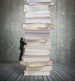 High stack of books with businessman climbing it. Reading and learning a mountain of new knowledge concept. Businessman climbing high stack of books on wooden royalty free stock photography