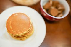 Stack of pancakes on white plate on wooden table in the kitchen . Breakfast or dinner for the whole family stock image
