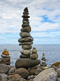 High stack of pebbles. On the beach and sea background Royalty Free Stock Images