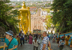 High stairs in the entrance to Batu caves in Kuala Lumpur. The crowd of pilgrims and tourists are visiting Batu Caves in Malaysia Royalty Free Stock Photography