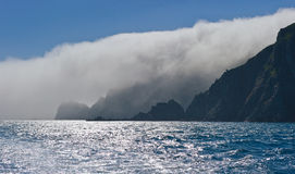 High, steep coast, covered in mist. Stock Photo