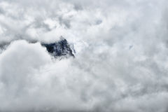 High and steep mountain surrounded by heavy clouds. In Glacier National Park Stock Images