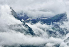 High and steep mountain surrounded by heavy clouds Stock Photo