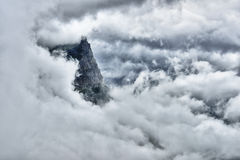 High and steep mountain surrounded by heavy clouds. In Glacier National Park Royalty Free Stock Photography