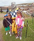 High Steward with children. High Steward wearing helmet and chain mail posing with three children attending the traditional Portsoy Boat Festival on Stock Photography