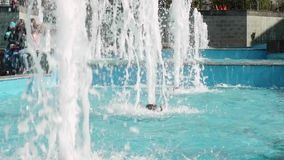 High streams of fountain in centre of small town. Blue water of pool. Sunny day with warm weather in town centre. High streams of fountain in centre of small stock video footage