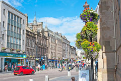 High Street, Inverness. Scotland with flowers outside the Town House and the Poundland shop prominent and beyond it a pedestrian walk Stock Image