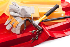 High-strength plastic roof. Red and yellow roof, hammer, screws, gloves, scrap, and the plummet Stock Photos