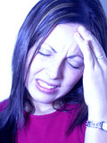 High Stress. Blue toned image of an extremely stressed out young woman rubbing her forehead Royalty Free Stock Photos