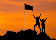 High success, Two people silhouette make high hand. With flag of victory on top of mountain, hands up Conceptual teamwork,business teamwork. Against the Stock Images