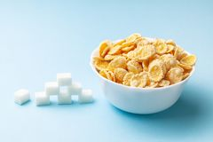 High sugar in flakes. Pile of sugar cubes and plate with cereal on blue background. High sugar in flakes. Pile of sugar cubes and plate with cereal on blue royalty free stock image