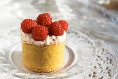 High tartlets with cream and raspberries on white tablecloth, selective focus Stock Photo